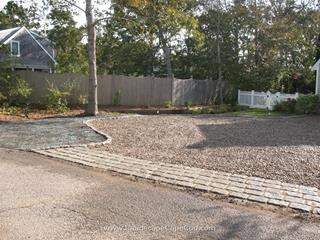 Failing asphalt driveway is removed and replaced with a cobble edged stone driveway.