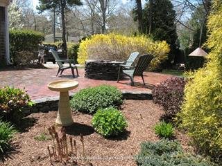 Antique red brick patio with a natural stone fire pit