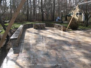 Travertine stone patio with veneered stone sitting wall and fire pit.